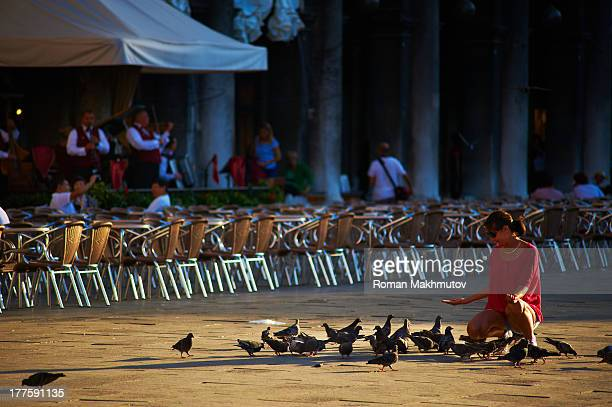 CONTENT] Tourist on Square Piazza San Marco feeding pigeons in front of street restaraunt