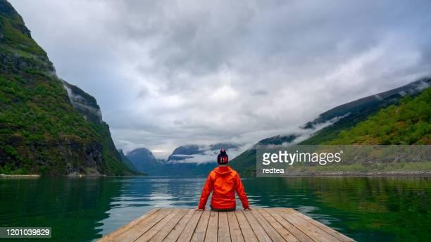 toerist op gezichtspunt stegastein, noorwegen - noorwegen stockfoto's en -beelden