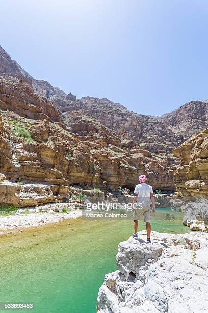 Tourist on the edge of canyon in rocky valley Oman