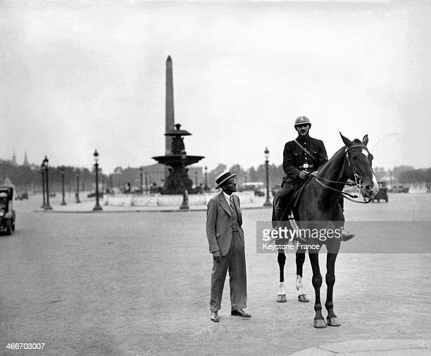 A tourist on the Place de la Concorde speaking with a mounted police officer in 1928 in Paris France