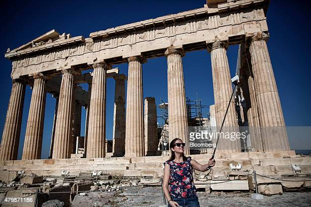A tourist operates her camera on a selfiestick as she stands beside the Parthenon temple on Acropolis Hill in Athens Greece on Wednesday July 8 2015...