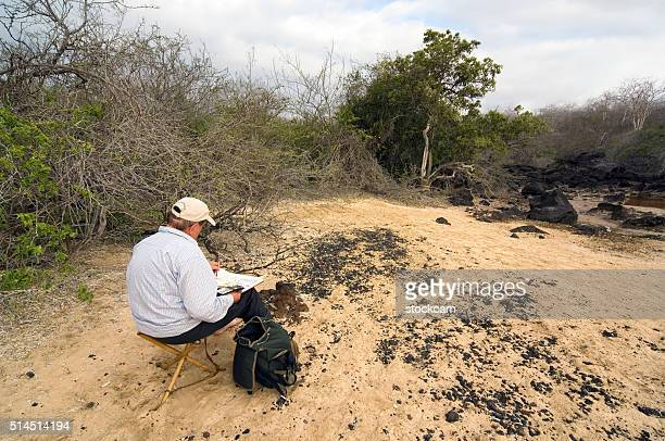 Tourist painting landscape on Mosquera island, Galapagos