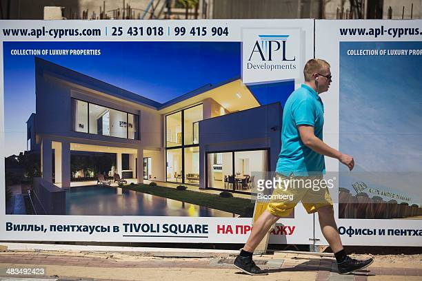 A tourist passes a billboard by the APL Group advertising luxury property for sale in Russian cyrillic script in Limassol Cyprus on Tuesday April 8...