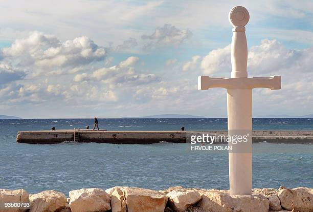A tourist passes a huge stonemade replica of legendary King Arthur�s sword in the stone in southern Croatian coastal town of Podstrana some 400...