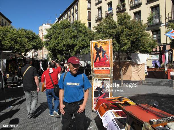 A tourist passing by a typical stall selling posters of flamenco and bullfighting in El Rastro Madrid Spain October 2011