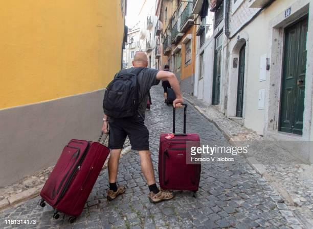 A tourist pauses while dragging his luggage uphill in Calçada Salvador Correia de Sa Santa Catarina historical neighborhood on October 15 2019 in...