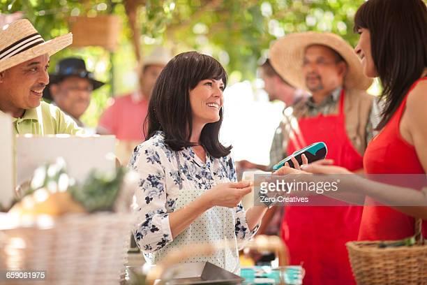 tourist paying market trader with credit card - groupe moyen de personnes photos et images de collection
