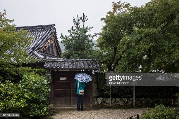 A tourist peaks through a gate at Tenryuji Temple on September 6 2015 in Kyoto Japan The famous city of Kyoto is going through a massive tourism boom...