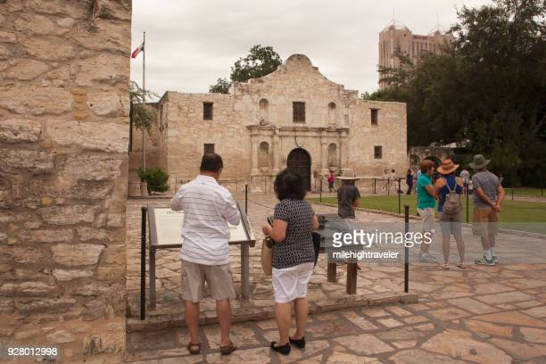 Tourist people walking visitors explore Alamo Spanish Mission San Antonio Texas