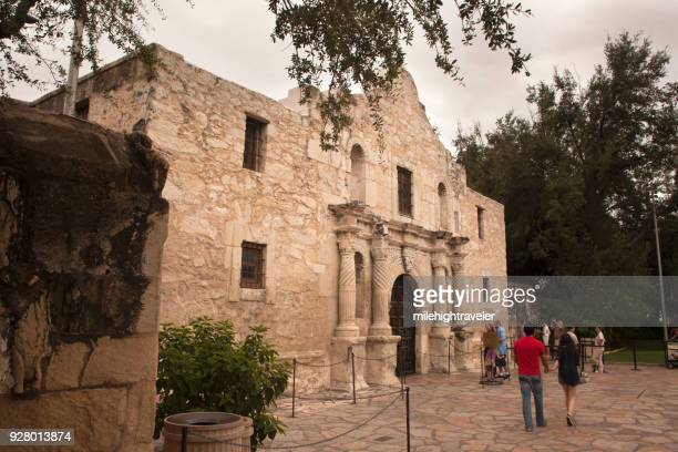 Tourist people walking visitors explore Alamo Spanish Mission San Antonio Texas