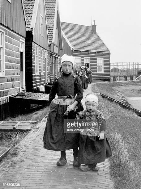 Tourist photo of traditionally dressed young children along a canal in Volendam The Netherlands