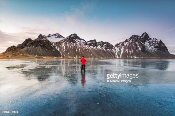 tourist photographer at stokksnes. iceland. - red coat stock pictures, royalty-free photos & images