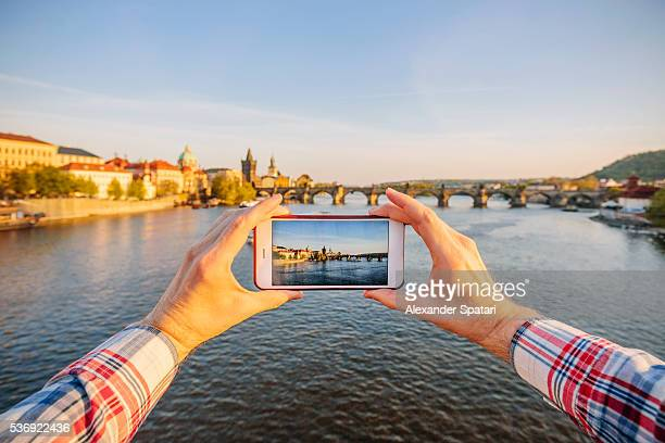 Tourist photographing Charles Bridge in Prague with smartphone