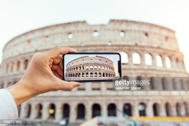 tourist photographing coliseum with smart phone, rome, italy - colosseum bildbanksfoton och bilder