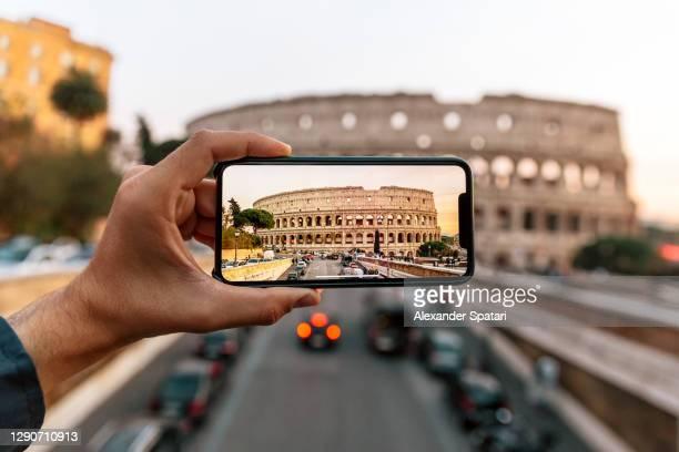 tourist photographing coliseum with smartphone, rome, italy - travel foto e immagini stock