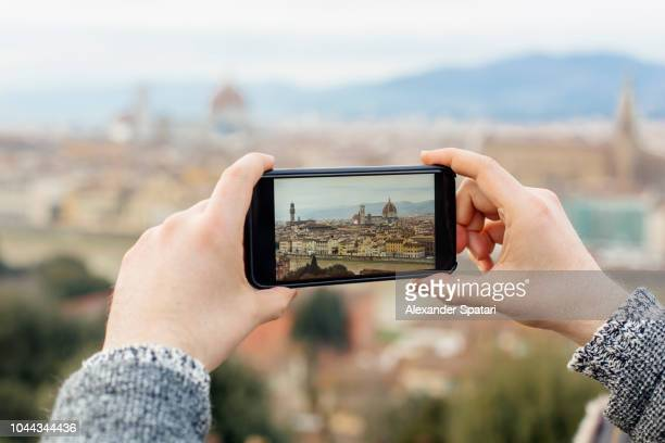 Tourist photographing Florence skyline with smart phone, Florence, Tuscany, Italy