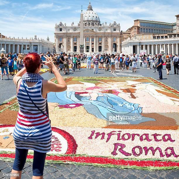 Tourist photographing flower petal art at Vatican City