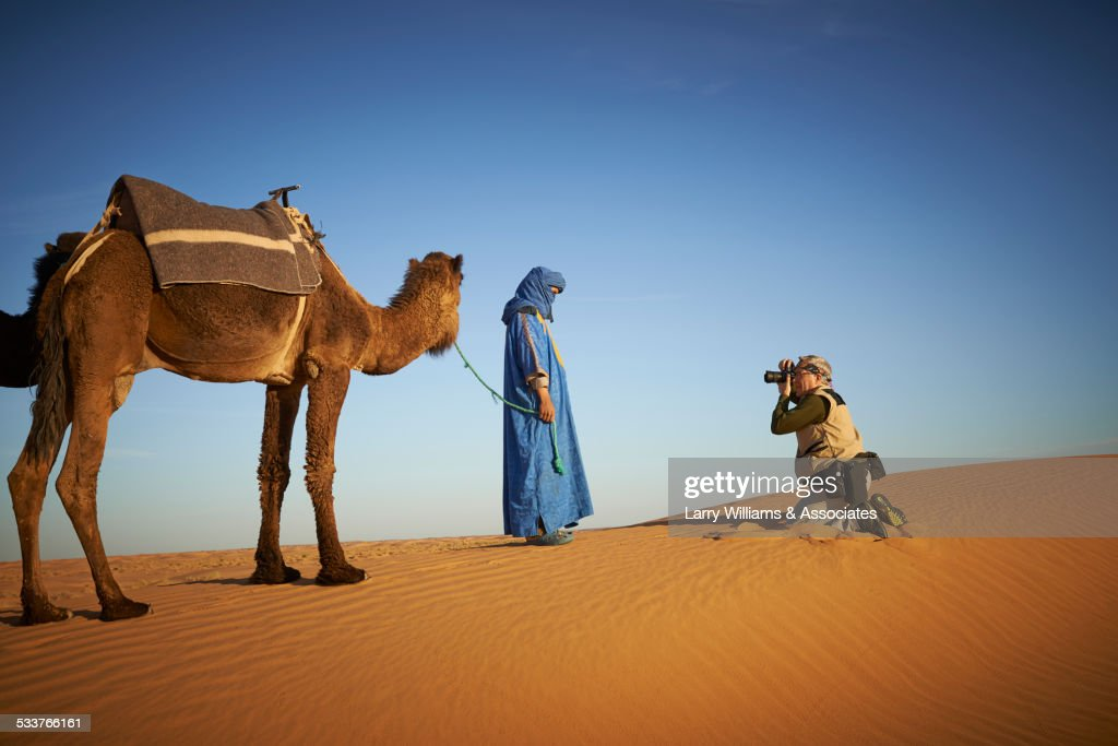 Tourist photographing guide with camel on sand dune in desert landscape : Foto stock