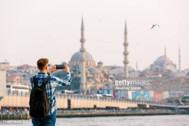 Tourist photographing Istanbul skyline with smart phone, rear view