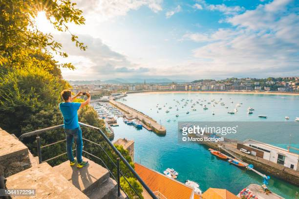 tourist photographing la concha bay and san sebastian, spain - eskapismus stock-fotos und bilder
