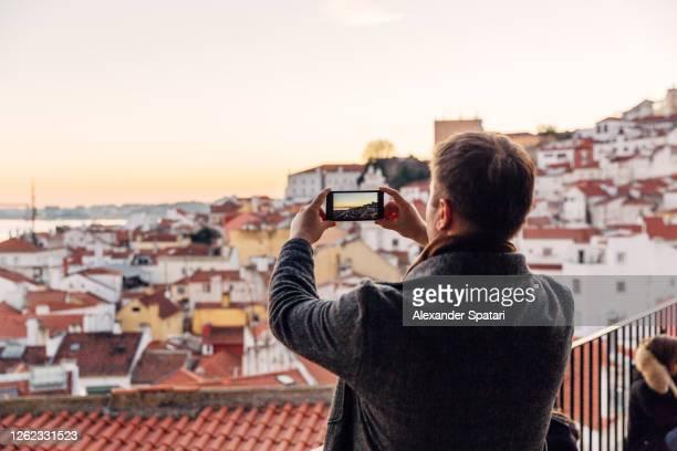 tourist photographing lisbon skyline at sunset using smartphone, portugal - モバイル撮影 ストックフォトと画像