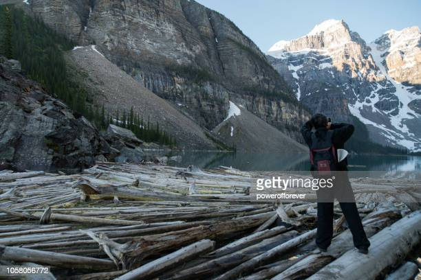 Tourist Photographing Moraine Lake in Banff National Park, Alberta, Canada