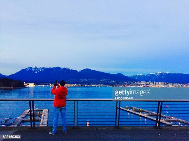 tourist photographing mountains in downtown vancouver - the lions stock photos and pictures