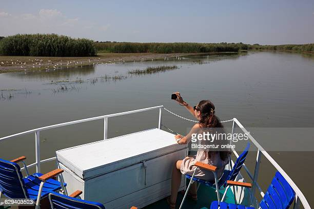Tourist photographing on an excursion boat in the Danube Delta Biosphere Reserve near Tulcea Romania