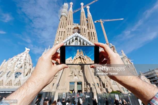 tourist photographing sagrada familia in barcelona with smartphone - familia stock-fotos und bilder