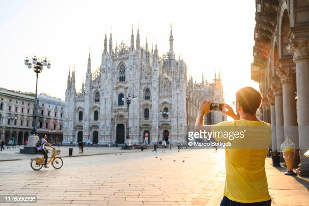 tourist photographing the cathedral (duomo) in milan with smartphone, italy - piazza del duomo milano foto e immagini stock