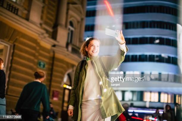 tourist photographing the night city with smart phone - multimedia stock pictures, royalty-free photos & images