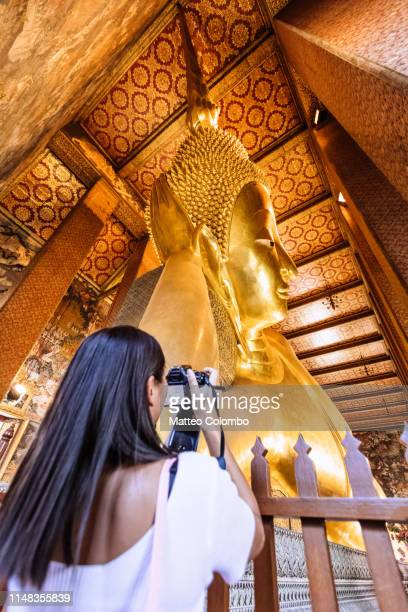 tourist photographing the reclining buddha, wat pho, bangkok - wat pho stock pictures, royalty-free photos & images