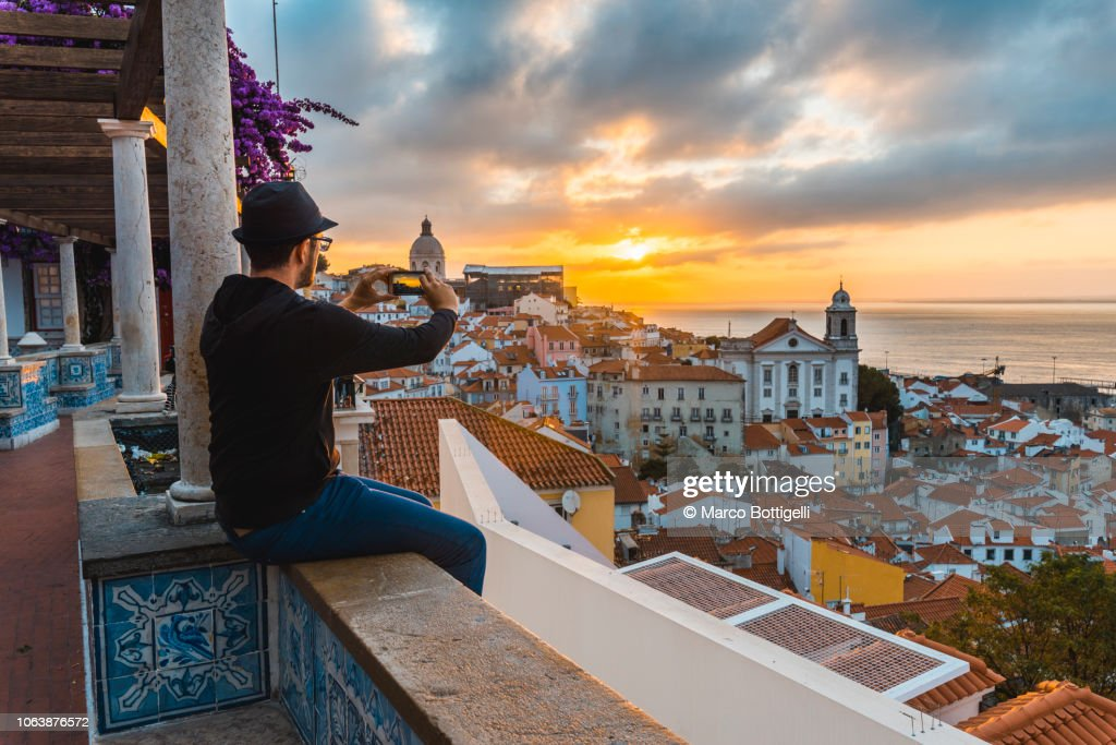 Tourist photographing with smartphone at sunrise in Lisbon, Portugal : Stock-Foto