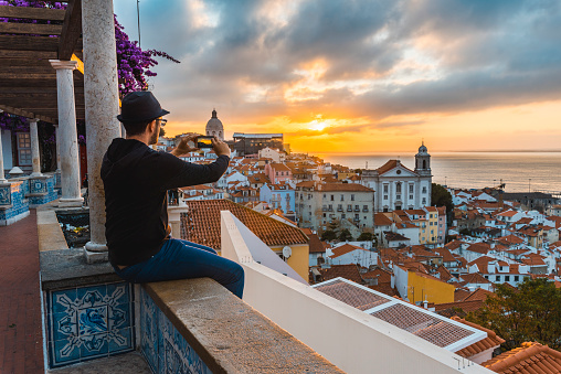 Tourist photographing with smartphone at sunrise in Lisbon, Portugal - gettyimageskorea