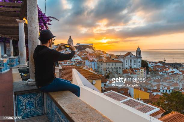 tourist photographing with smartphone at sunrise in lisbon, portugal - provincie lissabon stockfoto's en -beelden