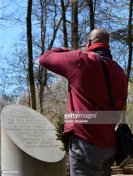 A tourist photographs a marker placed in memory of Afro Americans who served as slaves at Mount Vernon the plantation owned by George Washington the...
