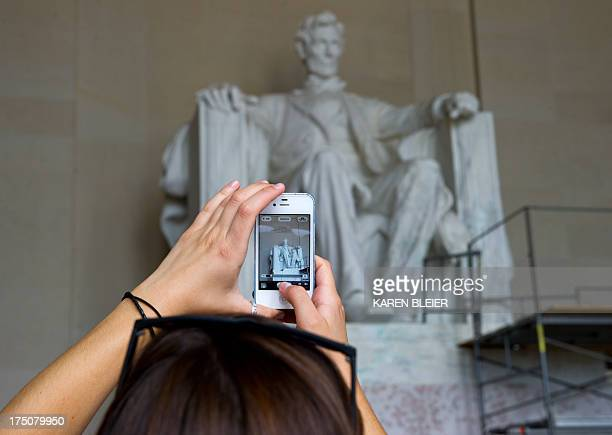 A tourist photographs a paint spattered statue of Abraham Lincoln July 30 2013 at the Lincoln Memorial in Washington DC Green paint was found early...
