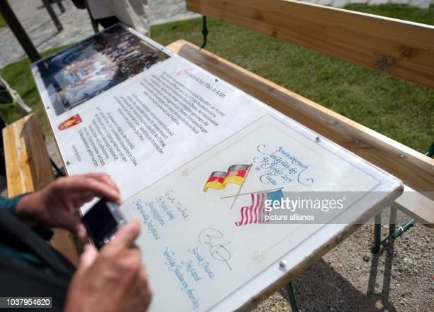 Tourist photographs a replica of the beer table at which President Obama sipped beer on 7 July 2015, in front of the town hall in Kruen, Germany, 19...