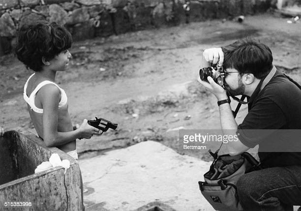 A tourist photographs a small girl clutching a toy revolver in the Vicigal shantytown in Rio de Janero Tour operatorshave started taking foreign...