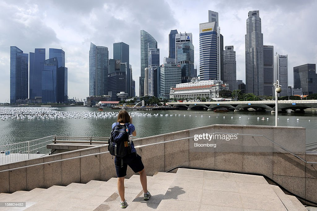 A tourist photographs office towers in the central business district in Singapore, on Sunday, Dec. 30, 2012. Singapore may grapple with elevated inflationary pressures for a third year in 2013, reducing scope for the central bank to provide stimulus to an economy that probably entered a technical recession this quarter. Photographer: Munshi Ahmed/Bloomberg via Getty Images