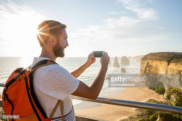Tourist photographs the Twelve Apostles using mobile phone