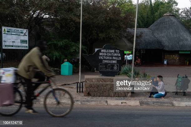 A tourist plays with a child next to a welcome sign with words 'MosiOaTunya' meaning Smoke that thunders at the entrance to the Victoria Falls...