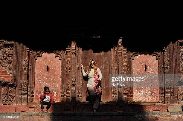 A Tourist pose as Nepalese Kid plays as taking sunbath around the premises of Basantapur Durbar Square Kathmandu Nepal on Tuesday December 13 2016