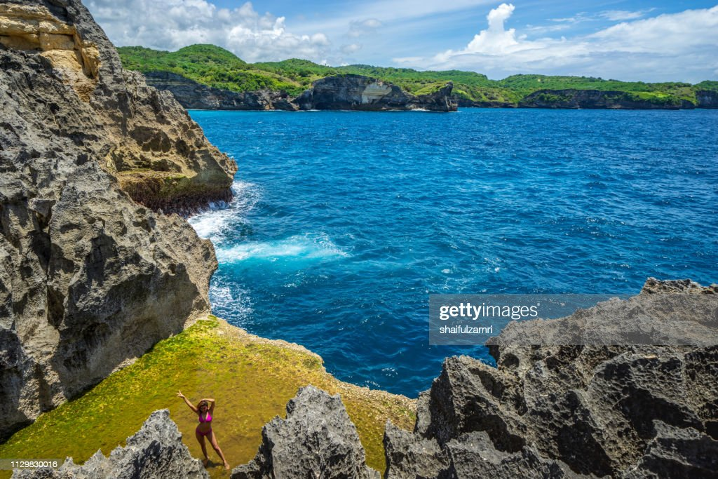 Tourist pose at Angel's Billabong, the natural pool on the island of Nusa Penida, Klingung regency, Bali, Indonesia. : Stock Photo