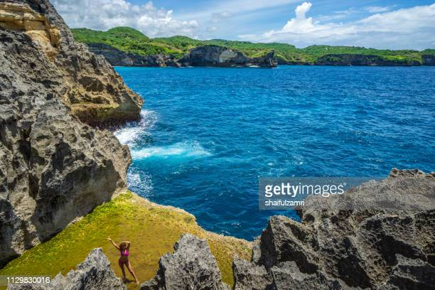 tourist pose at angel's billabong, the natural pool on the island of nusa penida, klingung regency, bali, indonesia. - shaifulzamri stock pictures, royalty-free photos & images