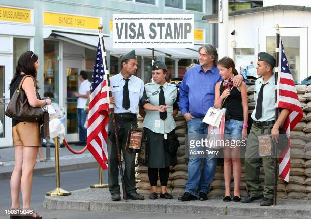 Tourist pose with performers dressed as American soldiers at Checkpoint Charlie on August 15 2012 in Berlin Germany In 2010 nine million tourists...