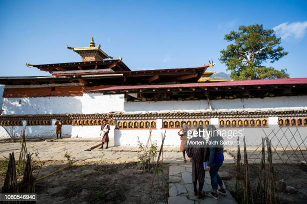 a tourist poses for a photo at kyichu lhakhang temple, bhutan springtime - paro district stock pictures, royalty-free photos & images