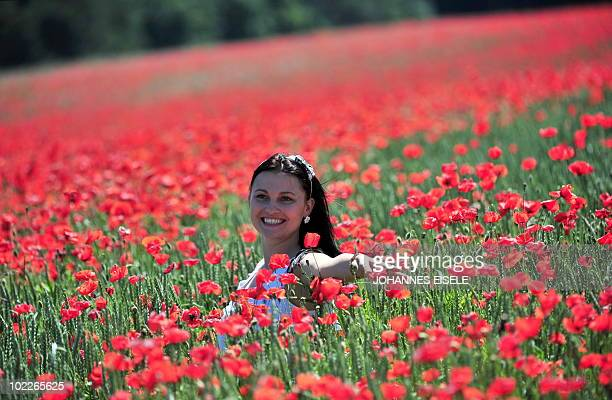 A tourist poses for a photo in a field of poppies near Luebben in the Spreewald region on June 17 2010 as the sun shines and temperatures in the...