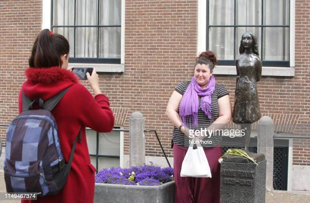 A tourist poses for a photo next the Anne Frank statue near Anne Frank houseremember Anne Frank's 90th Birthday on June 12 2019 in...