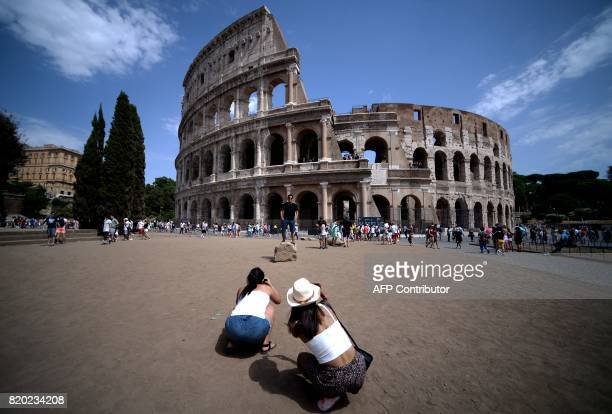 A tourist poses for a photo outside the Colosseum in Rome on July 21 2017 / AFP PHOTO / FILIPPO MONTEFORTE